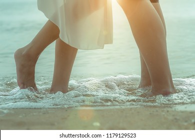 A loving couple on vacation. girl standing on tiptoes for a kiss. sunset sea. romance. only bare feet