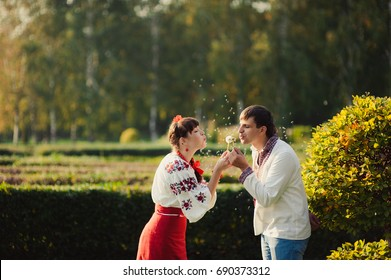 The loving couple on a walk blowing on a dandelion