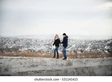 Loving couple on a walk in the winter on a hill in the woods. He warms her with his warm, running, hugging, jumping