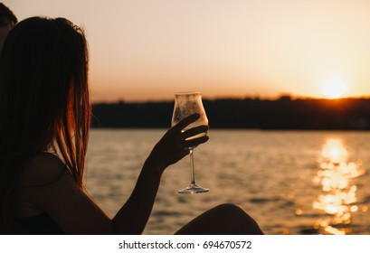 A loving couple on a yacht looks at the sunset. A girl is holding a glass of wine. Sea. The sun. Backlight