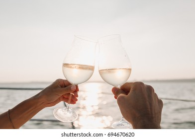 A loving couple on a yacht looks at the sunset and drinks wine.