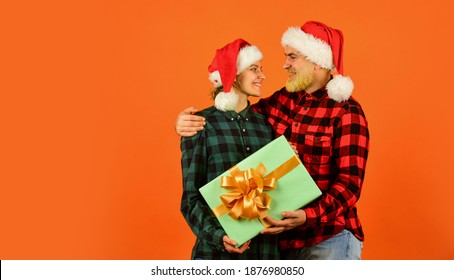 Loving couple orange background. Christmas magical time. We love christmas. Couple in love enjoy christmas holiday celebration. Family wear santa hats. Entertainment ideas for adults. Santa team.