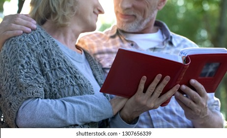 Loving couple with photobook tenderly looking at each other, pleasant moments
