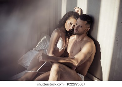 Loving couple posing in bedroom. Intimacy, sensual concept.