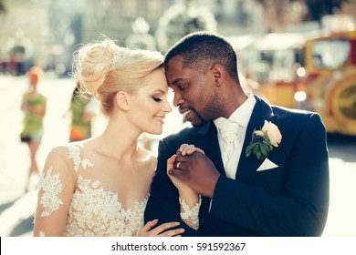 Loving couple of pretty girl or cute bride with beautiful blond hair in white sexy wedding dress and handsome man or african American groom outdoors on sunny day on blurred city street background
