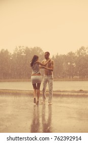 Loving couple in the rain barefoot. A man and a woman in love.