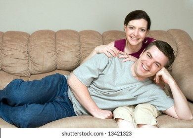 Loving couple relaxing on their couch together. He is lying on her lap. Both are looking at the camera with a smile on their faces. Horizontally framed shot.