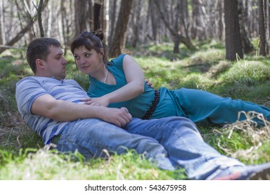 Loving couple resting on the nature. A guy and a girl lying on the grass in the shade of the trees.