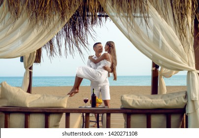 loving couple romantic dinner on seaside in bungalows,  honeymoon or  holiday - vacation concept. Man holds the girl on hands