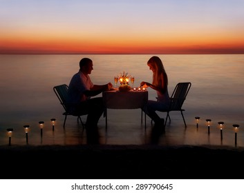 Loving couple share a romantic dinner with candles and lanterns light way at sea beach in water against wonderful sunset
