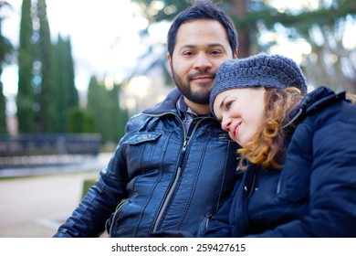 Loving couple sitting arm in arm on a park bench in warm winter clothing smiling happily at the camera