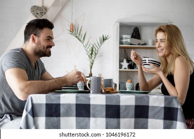 Loving couple sitting at a kitchen table, having a breakfast together.