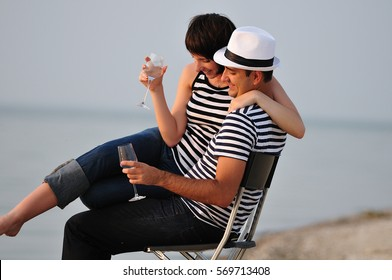 loving couple sitting on the beach with wine happy together