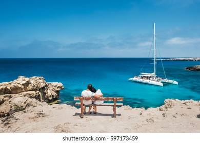 Loving couple sitting on a bench and looks at the lagoon. Honeymoon lovers. Man and woman on the island. Couple in love on vacation. A voucher for a cruise trip. Sea tour. Honeymoon trip. Cruise ship