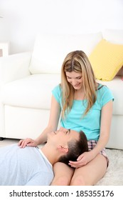 Loving couple sitting on carpet near sofa, on home interior background
