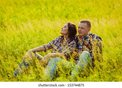 loving couple sitting on the grass in the field