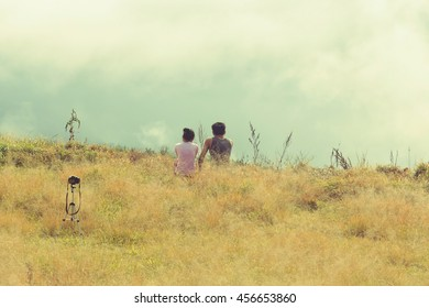 Loving couple sitting on the grass field and enjoying view of nature.