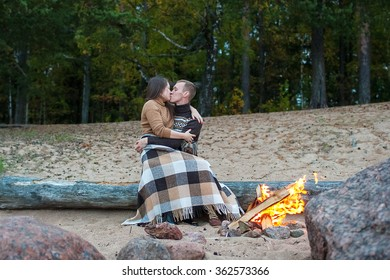 Loving couple sitting on a log by the fire on the rocky beach