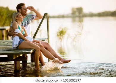 Loving couple sitting on the pier on lake at summer sunset