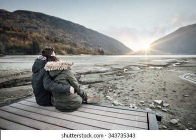 Loving couple sitting on a pier, hugging and looking away, love and feelings concept