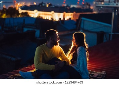 Loving couple is sitting on the roof of the house. In the distance, the lights of the night city.
