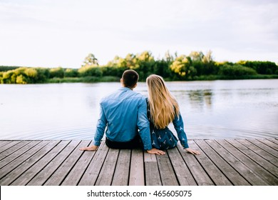 Loving couple sitting side by side on the pier. Male brunette and female blonde relaxing by the river at sunset. The guy and the girl model looking at the lake and enjoy nature.