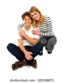 Loving couple sitting and smiling in front of camera