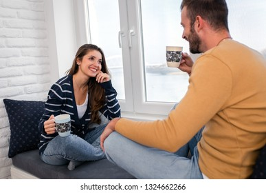 Loving couple sitting together by the window in the apartment and drinking coffee in the morning.