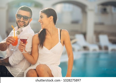 Loving couple spending vacation on tropical resort swimming pool.Newlyweds honeymoon on seaside.Couplr in true  love.Flirting and showing emotions.Affection.Celebrating anniversary.Happiness.Making a