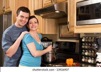 A loving couple standing in the kitchen cooking together.  Horizontally framed shot with both people looking at the camera.