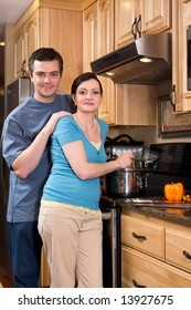 A loving couple standing in the kitchen cooking together.  Vertically framed shot with both people looking at the camera.