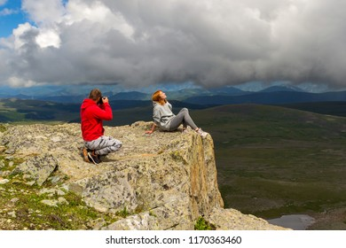A loving couple is standing on the mountain takes a photo of redhaired girl against the background of a valley bathed in sunlight,hills,blue lakes with glaciers, rocks with snow and white clouds.