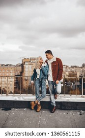 Loving couple is standing on the roof of the house in the city