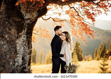 Loving couple stands near a tree in the mountains