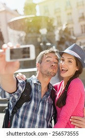 A loving couple is taking a selfie on their phone in the city . The woman is wearing   blue hat. The grey hair man is wearing a black backpack. They are looking at the camera with expressive faces.