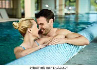Loving couple talking face to face while being in the water of indoor swimming pool at the spa.