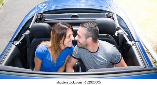 loving couple in their convertible car during the summer holidays