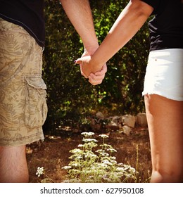 A loving couple with their hands together standing in a garden