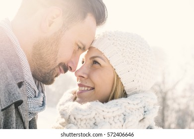 Loving couple touching foreheads and smiling while enjoying outdoors on sunny winter day