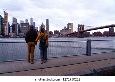 Loving couple tourists looking visit Brooklyn New York by the world famous Brooklyn Bridge at sunset