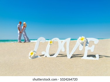 Loving couple at tropical ocean sandy beach with love word decoration and frangipani flowers. Proposal, wedding, valentines day or honeymoon background concept. Blonde woman in long dress and her man