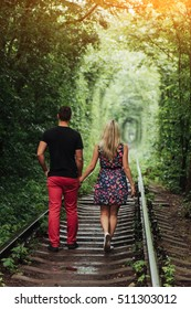 Loving couple in a tunnel of green trees on railroad