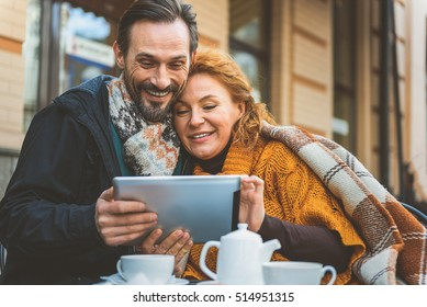 Loving couple using gadget in cafeteria