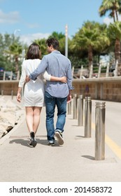 Loving couple walking away arm in arm along a beachfront promenade as they enjoy a vacation at the seaside