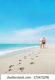loving couple walking away with footprints at sea sandy beach