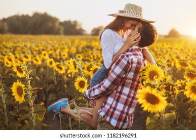 loving couple is walking in a blooming sunflower field. Sunset time