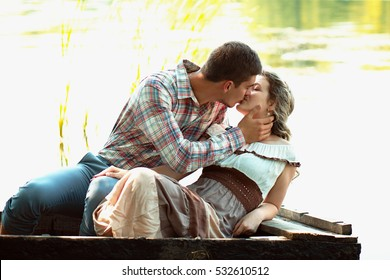 A loving couple walking by the lake outdoors summer sun warm beautiful