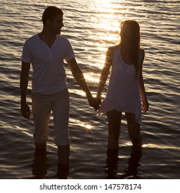 Loving couple walking by the sea at sunset