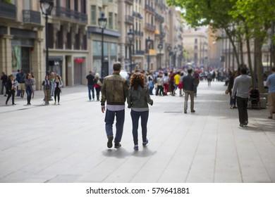 Loving couple walking down the streets of Barcelona, Spain. Light tilt shift effect applied.