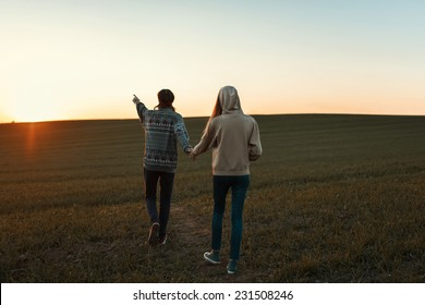 Loving couple walking towards the sunset on the field